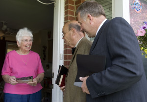 Diane Morrell, left, answers the door and talks to Jehovah's Witness members Gary Pickering and Richard Wolf. She's visiting from out of town but they still deliver a copy of The Watchtower and invite her to the July 3rd-5th convention in Ogden at the Dee Events Center. Al Hartmann/The Salt Lake Tribune 6/25/2009